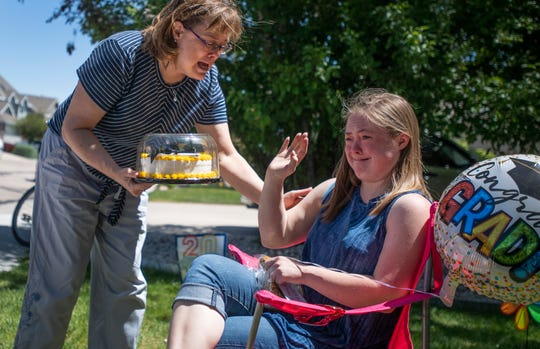 Kaeda MacMillan becomes emotional as Gayna Jobe, a transition teacher at the transitional learning program Cooper Home, hands her a graduation cake during a drive-by parade celebration in front of her home in Fort Collins, Colo. on Friday, May 22, 2020.