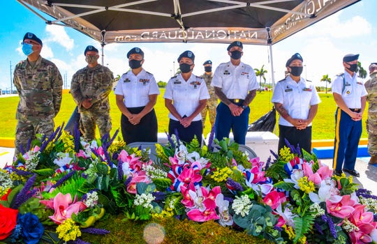 Guam National Guard members stand ready to present floral arrangements in memory of the fallen soldiers during a Fallen Heroes Memorial Ceremony at the Guam National Guard Joint Forces Headquarters in Barrigada on Friday, May 22, 2020.