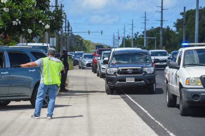 Motorists utilize an outer lane to line up for the Emergency Food Assistance Program, or TEFAP, in Piti on May 22, 2020.