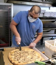 Tommy Rojas, co-owner of Tommy's Pizza Shoppe slices up a pie. Hagåtña, Guam, May 21, 2020.