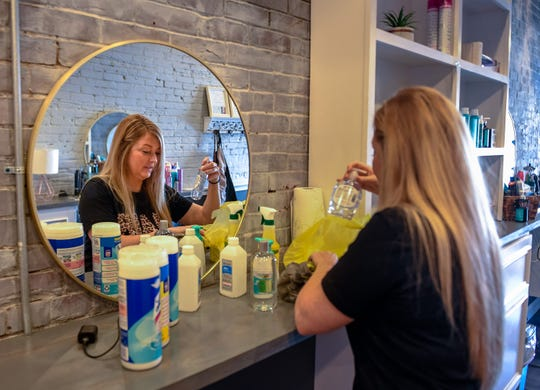 """Owner Katrina Payne, unpacks sanitizer supplies as she prepares her shop the """"Beauty Box Salon"""" for opening in a new world as business start to open since the COVID-19 lockdown Friday, May 22, 2020."""