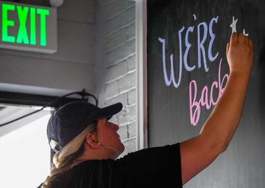 """Artist Kaylynn Poole draws a welcome back message on the blackboard as the """"Beauty Box Salon"""" prepares for opening in a new world as business start to open since the COVID-19 lockdown Friday, May 22, 2020."""