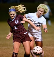 Henderson County's Hayley Rickard (left) beats out Madisonville's Halle Cunningham for possession during the 2014 Second Region final in Madisonville.