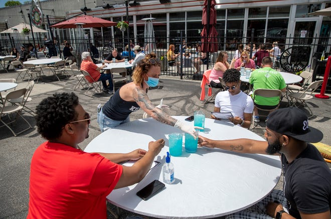 Beverages and diners at a newly-installed outdoor area in the parking lot next to Kilroy's, a sports bar in Broad Ripple, Indianapolis, Friday May 22, 2020. This location is adjacent to a blocked-off Broad Ripple Avenue, part of an experiment by the city to encourage more dining at eateries in a few high-traffic areas.