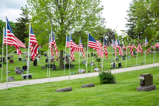 American flags line the road through Oak Hill Cemetery prior to Memorial Day during the novel coronavirus, COVID-19, pandemic, Friday, May 22, 2020, in Coralville, Iowa.