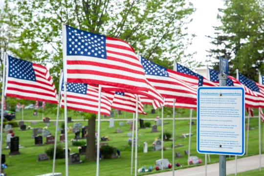A sign at Oak Hill Cemetery lists policies about decorations on graves as American flags line the road prior to Memorial Day during the novel coronavirus, COVID-19, pandemic, Friday, May 22, 2020, in Coralville, Iowa.