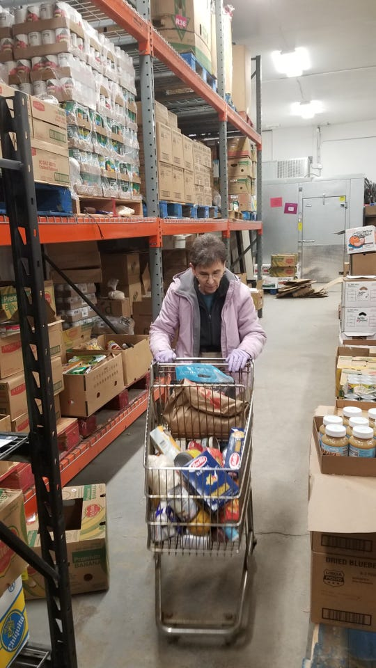 Marianne Burlew gets ready to pack food for a family that is unable to go to the Enfield Food Pantry.