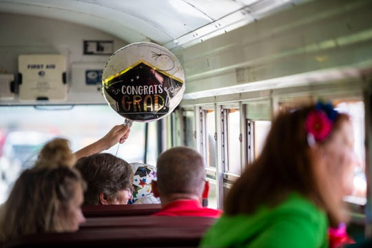 Dianae Hamonds, Supervisor of Humboldt High School holds a Congrats Grad Balloon as she looks out the window with the other staff and teachers of the Humboldt school district.