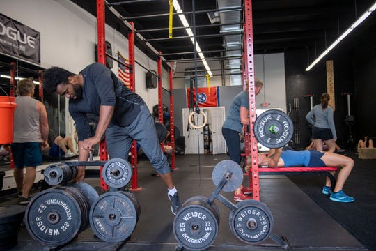 Atlas Fitness member, Chris Tucker picks up a weight in the gym, Thursday, May 22, 2020 in Jackson, Tenn. Kristen White, gym coach, has continued with gym classes and stays connected with her members via social media.