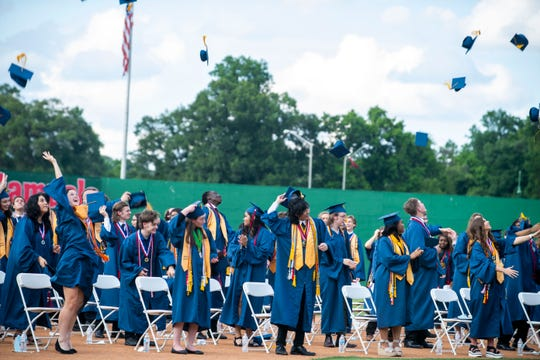 Madison Academic Magnet High School throw their hats in the air after their graduation ceremony at the Jackson Generals Ballpark in Jackson, Tenn., Thursday, May 22, 2020