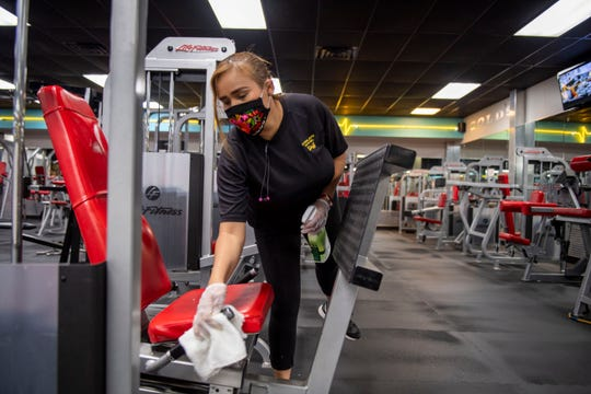 Gold's Gym staff member, Reyna Tortesgil, wipes down the gym and disinfects the equipment, Thursday, May 21, 2020 in Jakcson, Tenn.