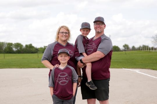 Janessa and Travis Martin pose for a photo with their sons, Grady, 7, and Bodie, 4, on the diamond of their backyard baseball field, Friday, May 22, 2020 in Linden.