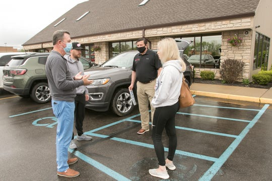 Wearing masks to protect their customers, Pinckney Chrysler Dodge Jeep Ram owner Dan Hall, left, and salesman Sergei Kharin talk to customers Payton and Matthew Charles about the Jeep Compass they consider for a lease in front of the dealership Friday, May 22, 2020. Transactions take place outside the dealership for health safety concerns.