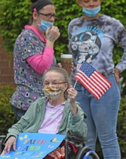 """A resident at Lexington Court Care holds a sign saying """"Faith and family"""" as a parade of vehicles carrying friends and family passes by."""