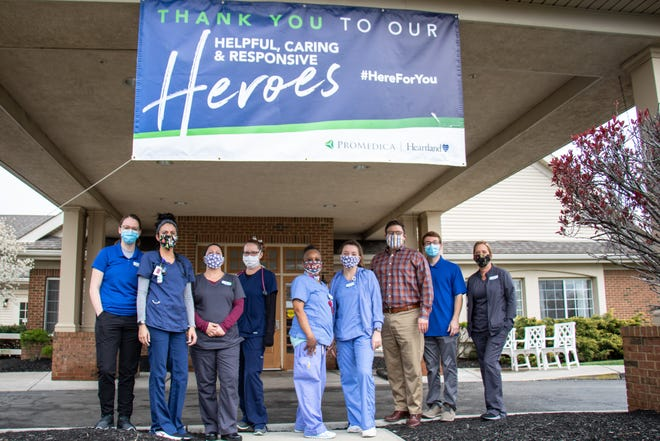 Doctors and nurses of Heartland of Marion, pose under the heroes sign with their masks on.