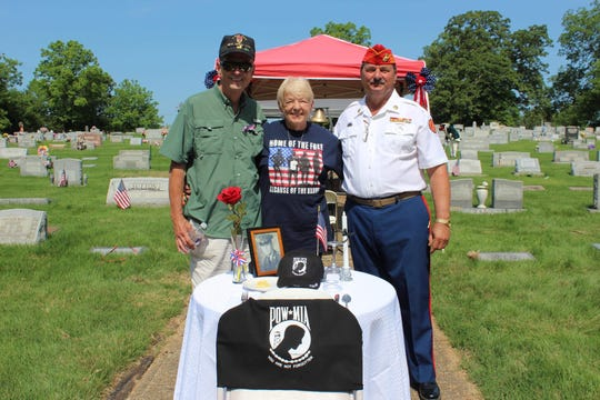 Sue O'Brien, center, stands in front of the missing man table she presented at Olive Branch's Memorial Day ceremony in 2018.  At right is Dave Szymanski, who coordinates the ceremony each year and will oversee this year's smaller ceremony being livestreamed for the first time