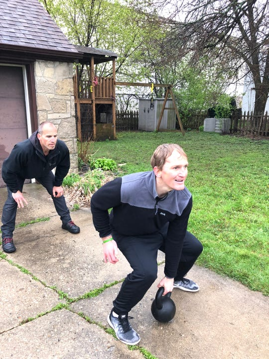 Trainer Garrett Stangel works with Justin Greenwood, holding a 50-pound kettlebell, in the driveway of Greenwood's Glendale home. Safer-at-home social distancing during the pandemic closed all essential small businesses, like the gym.
