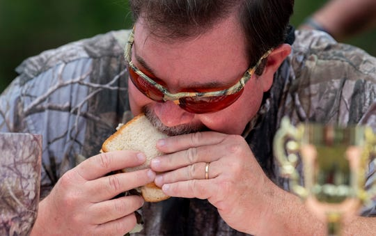 Montgomery Advertiser reporter Marty Roney takes part in a pickled pigs ear sandwich eating contest to help the Autauga County Probate Office Future Voter Program in Prattville, Ala., on Friday May 22, 2020.