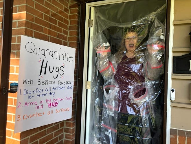 So she could hug her students, Kelsey Pavelka created a plastic barrier over her front door.