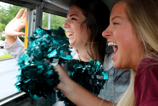 Black Fox Elementary 1st grade teacher Katie Beck left and Ali Flippo, Special education EA, right wave to students and passers-by during the school's bus parade on Thursday, May 21, 2020. The parade passed through student's neighborhoods to say an official good-bye to the students.