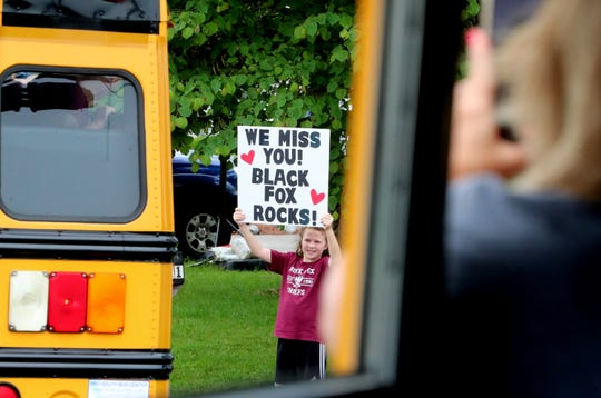 Black Fox Elementary students gather in their neighborhoods to wave at the Black Fox bus parade on Thursday, May 21, 2020. The parade passed through student's neighborhoods to say an official good-bye to the students.