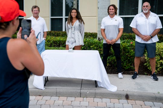 Brooke Hornbeck, left, takes a photo of First Baptist Academy senior Malaya Melancon, center, recipient of the Winged Foot Scholar-Athlete Award, as she poses alongside Bud Hornbeck, center left, Winged Foot Scholar-Athlete Award chairman, Michael Walker, center right, the 2015 award recipient and wide receiver for the Jacksonville Jaguars, and Mike Walker, right, Winged Foot Scholar-Athlete Award board member, at Gallagher Lutgert Insurance in Naples on Friday, May 22, 2020. Melancon is the first athlete from First Baptist Academy to win the award.