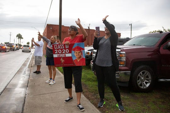 Community members including Julia Gomez, second from right, wave as Immokalee graduates make their way down South 1st Street on Friday, May 22, 2020, in Immokalee. Gomez was out to support her nephew Immokalee High senior Austin Anzualda during his graduation parade.
