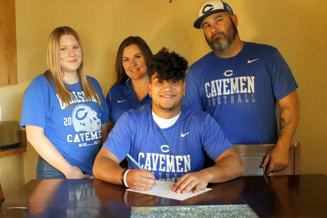 Carlsbad's Eli Etheridge signs his commitment letter to attend Western New Mexico University with his parents on May 21, 2020.