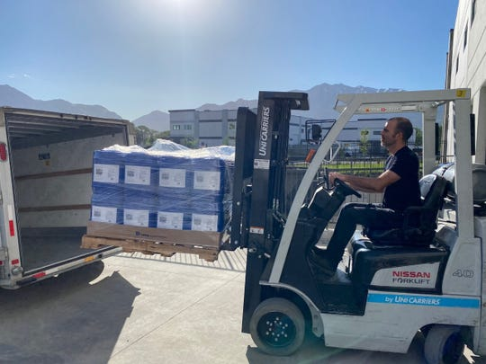 Five-gallon jugs of hand sanitizer produced by Ogden's Own Distillery are loaded into a trailer for delivery from Ogden, Utah to Shiprock on May 19.