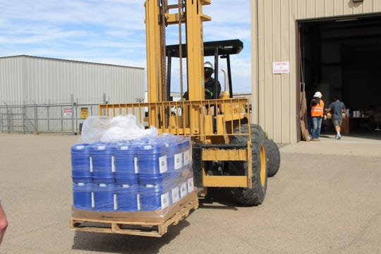 Multiple gallons of hand sanitizer are transported to the NECA Warehouse for distribution on Tuesday, May 19, 2020, in Shiprock. Ogden's Own Distillery of Ogden, Utah, donated 485 gallons of hand sanitizer.