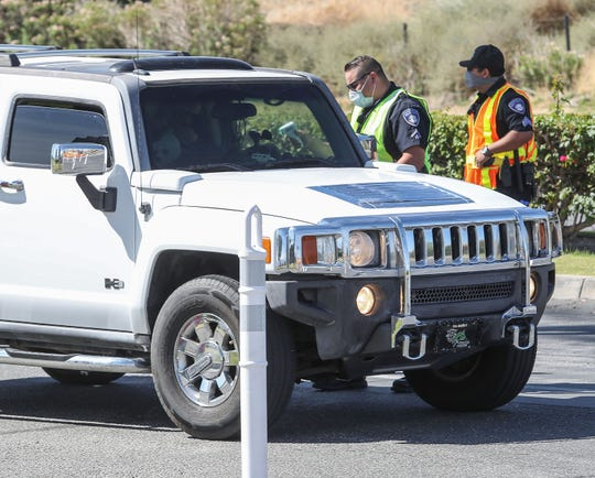 Security checks the temperature of occupants of vehicles coming into the Spotlight 29 Casino during its reopening in Coachella, May 22, 2020.