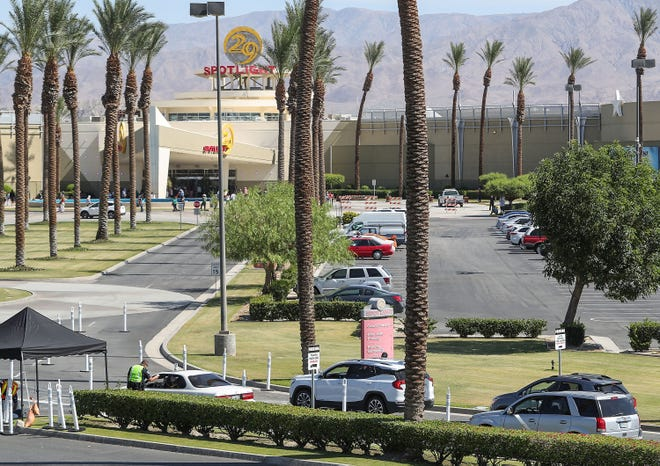 Security personnel, lower left, check the temperature of guests coming into the Spotlight 29 Casino during its reopening in Coachella, May 22, 2020.