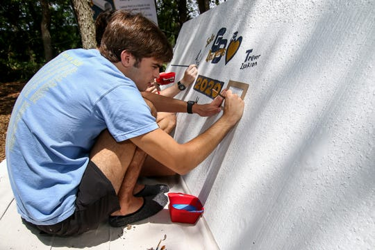 Gulf Breeze High School senior Britton Landrum signs his name to a new installation at Lookout Point near Shoreline Park in Gulf Breeze on Friday, May 22, 2020. The 7-ton piece of concrete is from a section of the Pensacola Bay Bridge that is being demolished during construction of the new bridge.