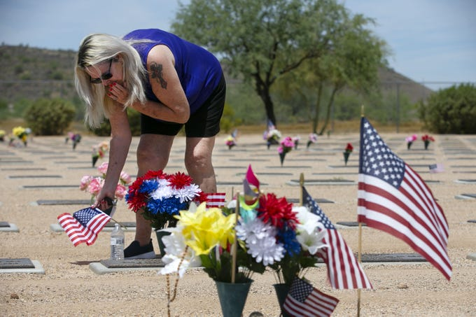 On the Friday before Memorial Day, Nel Reif, of Goodyear, places a flag at the gravesite of her husband, Jeffrey Reif, at the National Memorial Cemetery of Arizona in Phoenix on May 22, 2020. Jeffrey, a veteran of the U.S. Army who served in the Vietnam War, died in 2015 from complications related to Agent Orange.