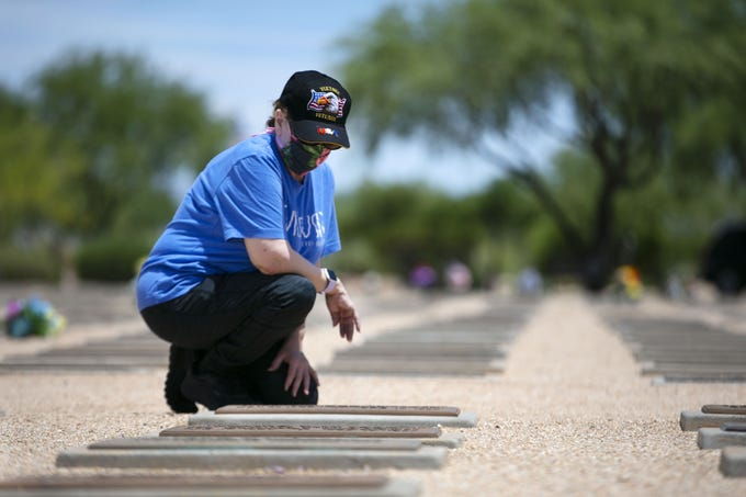 On the Friday before Memorial Day, Rosemary Sweeney, of Gilbert, visits her husband's gravesite at the National Memorial Cemetery of Arizona in Phoenix on May 22, 2020. Rosemary's husband, William John Sweeney, a veteran of the U.S. Army, served during the Vietnam War. Her father, Edward Brooks, a veteran of the U.S. Navy, served in World War II and is buried at the National Memorial Cemetery of Arizona. He is buried with Rosemary's mother, Nancy Brooks.