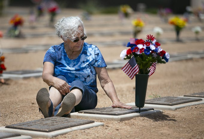 On the Friday before Memorial Day, Margie Lugo, of Youngtown, visits the gravesite of her husband, Louis Lugo, at the National Memorial Cemetery of Arizona in Phoenix on May 22, 2020. Louis, a veteran of the U.S. Army who served in the Korean War, was a recipient of the Purple Heart. He passed away in October 2019.