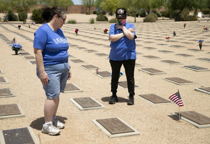 On the Friday before Memorial Day, sisters Nancy Munoz (left) and Rosemary Sweeney, both of Gilbert, visit their parents' gravesite at the National Memorial Cemetery of Arizona in Phoenix on May 22, 2020. Their father, Edward Brooks, a veteran of the U.S. Navy, served in World War II. He is buried with their mother, Nancy Brooks. Sweeney also visited the gravesite of her husband, William John Sweeney, a veteran of the U.S. Army, who served during the Vietnam War.