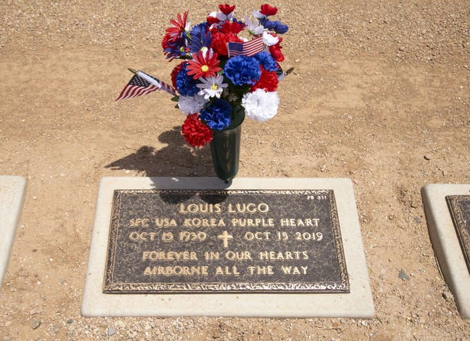 On the Friday before Memorial Day, flowers and American flags adorn the gravesite of Louis Lugo, a U.S. Army veteran who served in the Korean War and received the Purple Heart, at the National Memorial Cemetery of Arizona in Phoenix on May 22, 2020.