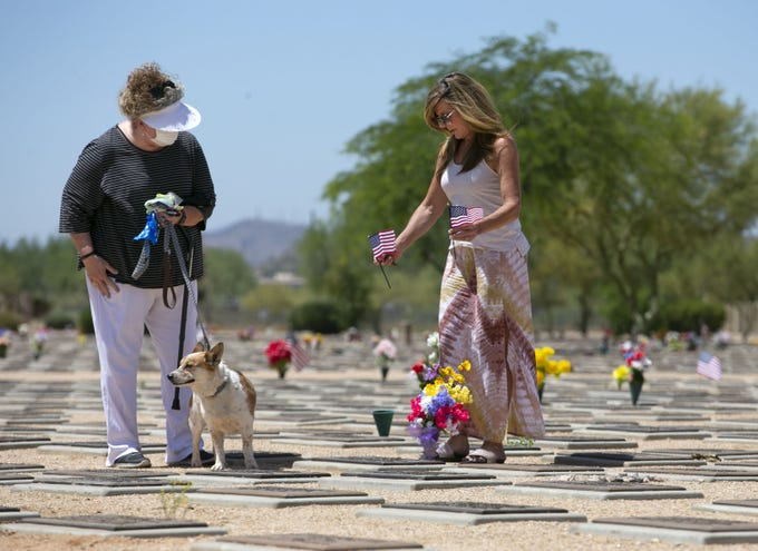 On the Friday before Memorial Day, sisters Liz Kelley (left), of Oklahoma City, Oklahoma, and Colleen Laney, of Scottsdale, visit at the gravesite of family friends, at the National Memorial Cemetery of Arizona in Phoenix on May 22, 2020. Kelley holds on to her dog, Tanner. They were visiting the site of Frank Reimers and his wife, Carol Reimers. Frank was a veteran of the U.S. Navy and served in World War II.