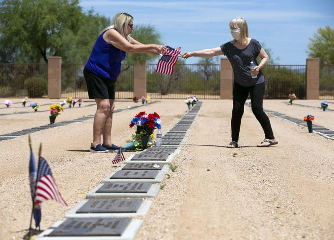 On the Friday before Memorial Day, Bridget Gibson (right), of Phoenix, hands flags to her friend, Nel Reif (left), of Goodyear, as Reif places the flags at the gravesite of her husband, Jeffrey Reif, at the National Memorial Cemetery of Arizona in Phoenix on May 22, 2020. Jeffrey, a veteran of the U.S. Army who served in the Vietnam War, died in 2015 from complications related to Agent Orange.