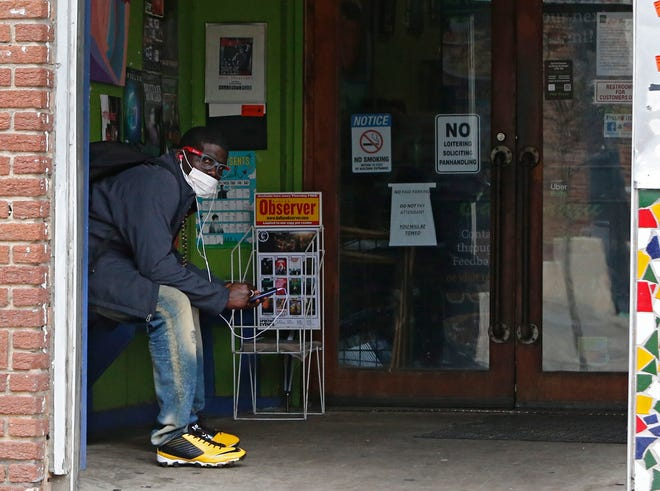 Un hombre que llevaba una máscara se sienta en la entrada de un restaurante cerrado, en Dallas, Texas, EE.UU.
