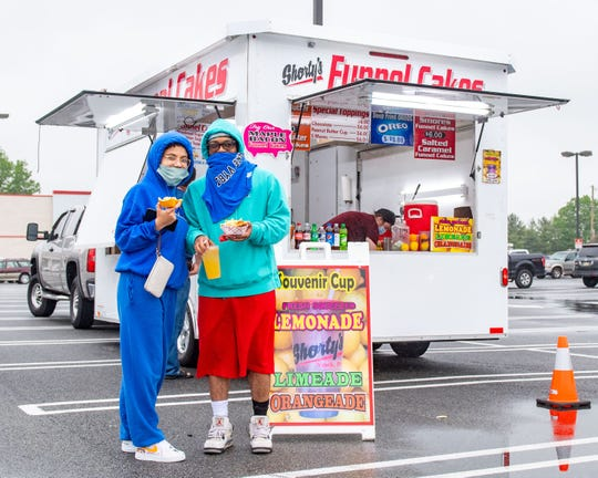 """With many areas moving into the """"yellow"""" phase of reopening on Friday, Dewayne Pinnock (right) and Nathaly Fermin (left) of Dallastown take advantage of a food truck."""