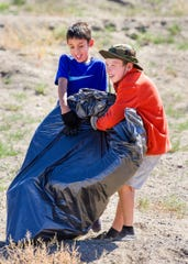 Isaiah Nunez, 9, and Jonah Manford, 8, wrestle a large bag of trash during Yerington's Y Hill Cleanup Day.