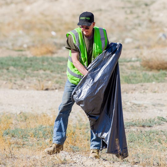 A volunteer picks up trash during Yerington's Y Hill Cleanup Day.