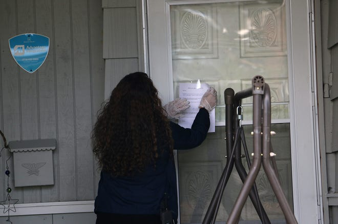 WCSD Attendance Officer Adriana Partida posts a notification from the district on the front door of a home in Sparks on May 22, 2020. The district is actively reaching out to families with children who have not had contact with their teachers since the schools shut down due to the COVID-19 pandemic.