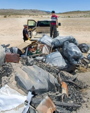 Chris Goodman and his son Stephen, 13, finish emptying the back of their pickup during Yerington's Y Hill Cleanup Day.