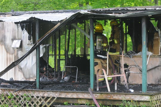 Richmond Fire Department members work inside a burned trailer Friday, May 22, 2020, in Garden City Trailer Park.