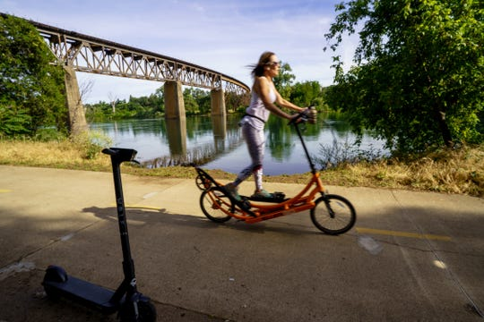 A woman on a scooter rides along the Sacramento River Trail in Redding on Friday, May 15, 2020.