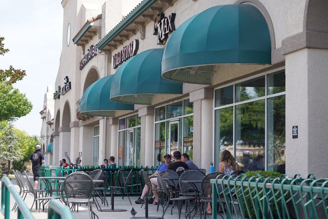 People sit outdoors during lunch hour Saturday, May 9, 2020 in the Discovery Village on Dana Drive in Redding. A stay home order on March 19 forced California restaurants to close dine-in services. Restrictions were loosened the following week.