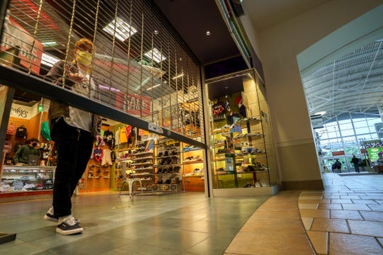 A store employee opens the screen gate on reopening day at Mt. Shasta Mall on Monday morning, May 18, 2020, about two months since it closed due to the COVID-19 pandemic.